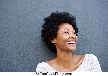 Close up smiling woman against gray wall