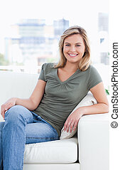 Close up, smiling woman with crossed legs sitting on couch