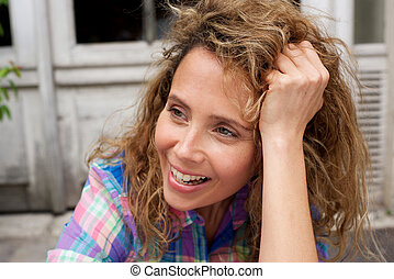 Close up smiling woman with curly hair looking away