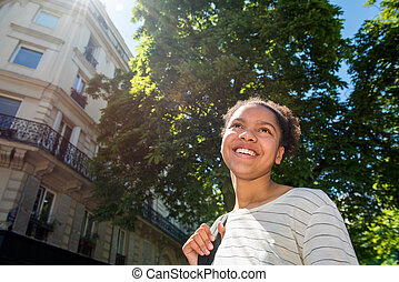 Close up smiling young african american girl with bag outdoor