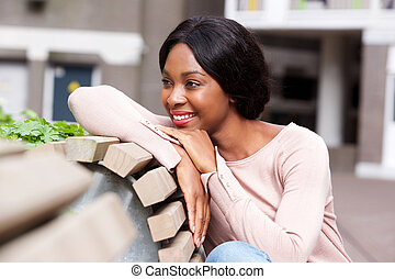 Close up smiling young african american woman sitting on bench outside