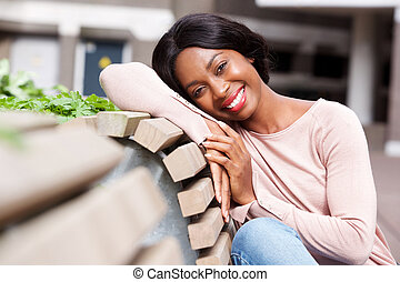 Close up smiling young african american woman sitting outside on bench