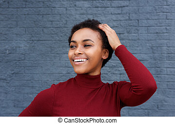 Close up smiling young black woman with hand in hair