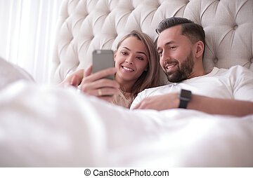 young couple reading e-mails on their smartphone