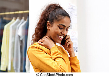 Close up smiling young indian woman talking with mobile phone