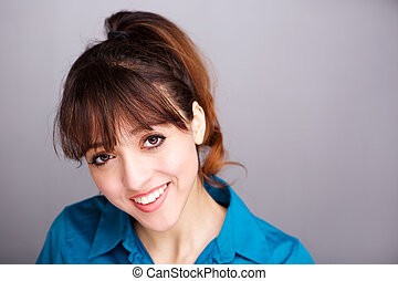 Close up smiling young woman against gray wall