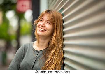 Close up smiling young woman leaning against wall and looking away