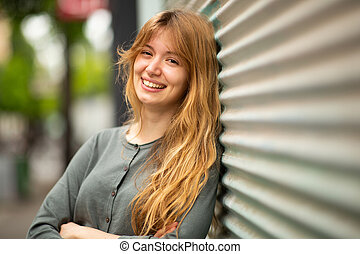 Close up smiling young woman leaning against wall outside