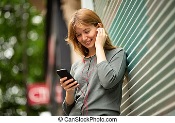 Close up smiling young woman listening to music with earphones and cellphone outside
