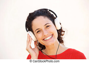 Close up smiling young woman listening to music with headphones
