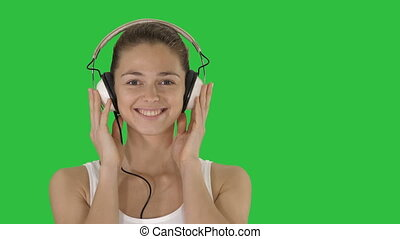 Smiling young woman listening to music with headphones on a Green Screen, Chroma Key.