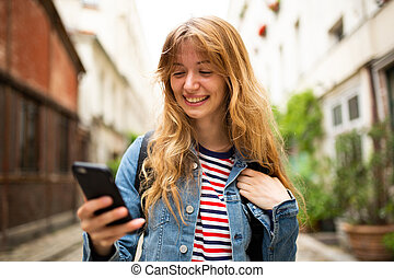 Close up smiling young woman looking at mobile phone in city