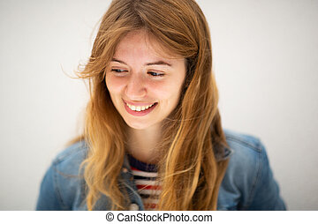 Close up smiling young woman looking down by white background