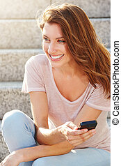 Close up smiling young woman sitting with mobile phone