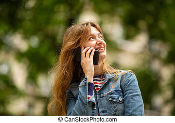 Close up smiling young woman talking with cellphone in park