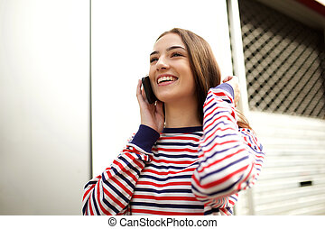 Close up smiling young woman walking and talking with mobile phone