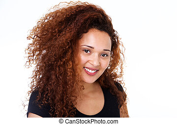 Close up smiling young woman with curly hair against isolated white background
