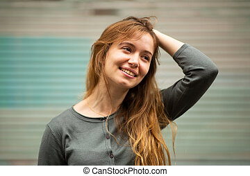 Close up smiling young woman with hand in hair