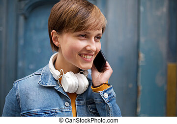 Close up smiling young woman with short hair talking with mobile phone