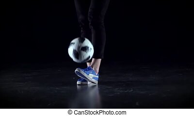 Close-up soccer player's legs making tricks with ball at...