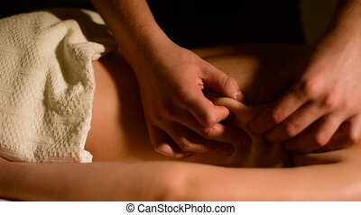 Close-up spa massage woman's shoulders and back. Male hands do massage to a woman in a dark room with candles in the background