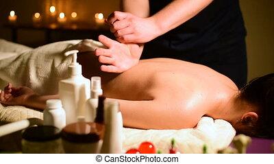 close-up, spa, masseren, van een vrouw, schouders, en, back., mannetje hands, doen, masseren, om te, een, vrouw, in, een, donkere kamer, met, kaarsjes, in, de, achtergrond
