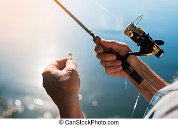 Close up. Spinning with a reel in the right hand, hook with bait in the left hand against the background of water