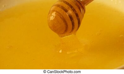 Close up spinning wooden dipper in honey bowl - Close up...