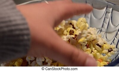 Close up static shot of glass bowl filled up with pop corns and couple reaching out for it enjoying some quality time together. Bonding concept, friendship and relationship.