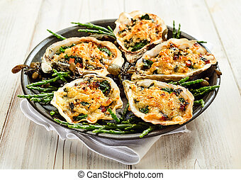 Close Up Still Life of Oysters with Cheesy Gratin Topping Served on Plate with Green Garnish on Painted Wooden Table