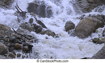 Close-up stones and spray of a stormy mountain river in slow...