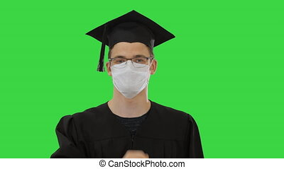 Student in gaduation gown and face mask stumbling on a Green Screen, Chroma Key.