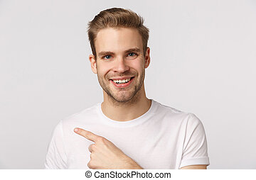 Close-up studio portrait charming blond man with bristle, pointing finger left as showing good product, pleased after visiting store, leave positive feedback, recommend promo, white background