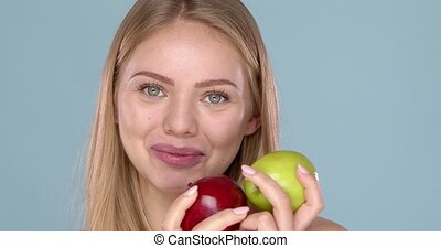 Close up studio shot of smiling young woman holding two ...