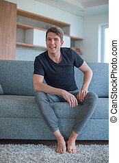 successful young man sitting on sofa in living room
