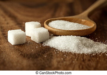 Close up sugar cubes and cane in wooden spoon on the table