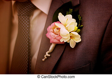 Close-up suit groom with tender flower buttonhole