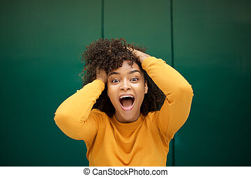 Close up surprised young african american woman with hands in hair and mouth open