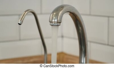 Close Up Tap water flowing from Kitchen faucet. Water...