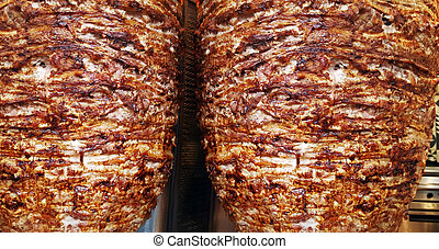 Close up texture of rotating skewered meat grilled - A pair...