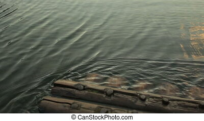 Close-up texture of waves on the mountain lake with wooden...