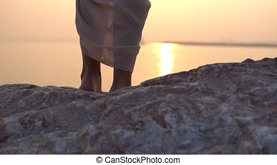 Close-up. The dress is developed in the wind against the background of sunset. slow motion