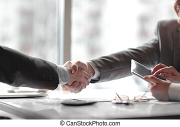 close up. the financial partners shaking hands over a Desk