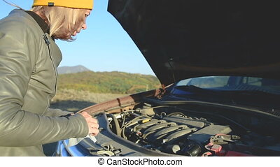 Close up The girl is trying to dig under the hood of the car...