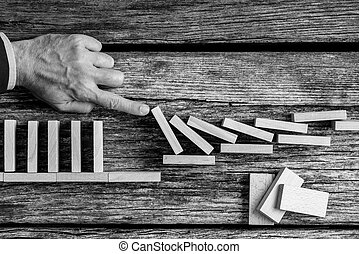 Close-up the hand of a man stopping domino effect
