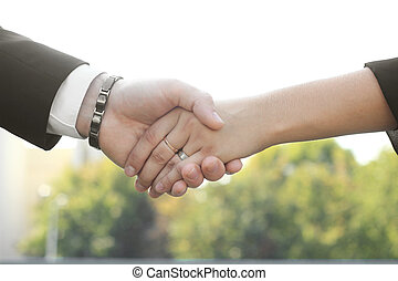 close up. the handshake business partners in the outdoors.photo with copy space.