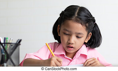Close up the little girl is doing homework intently