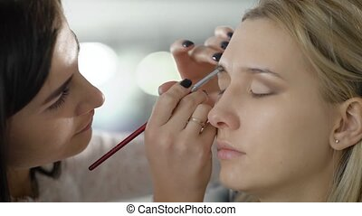 Close up. The master in a make-up prepares model for display. The girl puts with a slanting brush of a shadow for eyebrows. Smooth tone of the face, natural lips