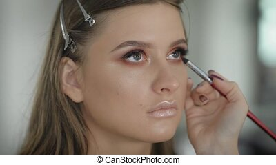 Close up. The master in a make-up trains the student for...