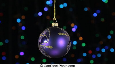 Close-up, the rotation of a lilac Christmas ball hanged on a golden rope. Christmas and New Year decoration. Abstract blurred bokeh holiday background. Blinking garland.